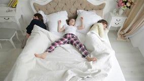 La familia feliz está descansando sobre la cama blanca Retrato de la madre dormida, del padre y de la pequeña hija en pijamas en almacen de metraje de vídeo