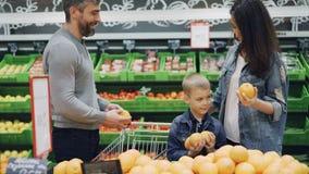 La familia feliz está eligiendo naranjas en el supermercado, padre de la madre y el muchacho lindo está tomando la fruta, oliéndo metrajes