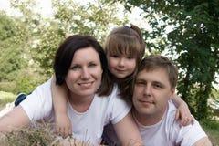 La familia feliz está en parque Fotografía de archivo libre de regalías