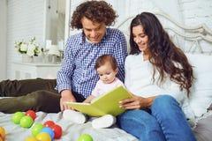 La familia feliz está leyendo un libro con un niño en el cuarto imagenes de archivo