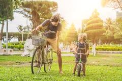 La familia feliz está montando las bicis al aire libre y la sonrisa Padre en un b fotos de archivo libres de regalías