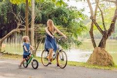 La familia feliz está montando las bicis al aire libre y la sonrisa Mamá en una bici imagenes de archivo
