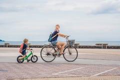 La familia feliz está montando las bicis al aire libre y la sonrisa Mamá en una bici fotografía de archivo