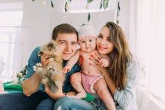 La familia feliz está sosteniendo el bebé y el conejo mientras que se sienta en el childroom Fotos de archivo