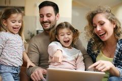 La familia feliz goza en casa Imágenes de archivo libres de regalías