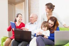 La familia goza en sitio de la sala de estar con pocos ordenadores portátiles Imágenes de archivo libres de regalías