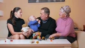 La familia feliz grande con un bebé su madre y abuelos se divierte en casa en el sofá Ríen y hablan entre metrajes