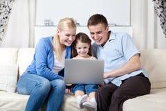 La familia feliz hace compras a través del Internet Foto de archivo libre de regalías