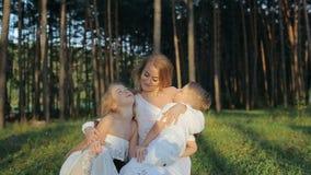 La familia feliz joven de tres que se divierten en la madre del bosque y los niños en la ropa y el sombrero de paja blancos son f almacen de metraje de vídeo