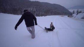 La familia feliz joven que se divierte que juega en un padre nevoso del bosque rueda a su poco hijo en un trineo Un paseo de la t almacen de video