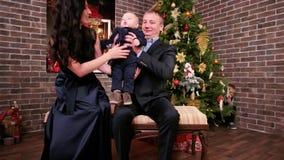 La familia feliz, madre da a un pequeño niño en manos encendido a su padre, familia con el bebé lindo en las manos, padres con almacen de metraje de vídeo