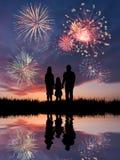 La familia mira los fuegos artificiales hermosos Imagenes de archivo