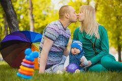 La familia feliz plaing en el parque Foto de archivo libre de regalías