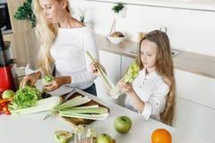 La familia feliz que cocina el desayuno sano junta se dirige la cocina Foto de archivo libre de regalías
