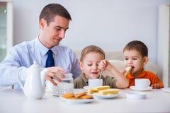 La familia feliz que desayuna junto en casa foto de archivo