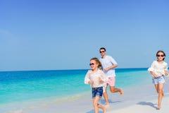 La familia feliz que disfruta de tiempo de la playa y se divierte mucho en la orilla Fotos de archivo libres de regalías