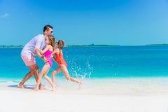 La familia feliz que disfruta de tiempo de la playa y se divierte mucho Foto de archivo libre de regalías