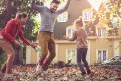 La familia feliz que salta en la caída se va en el patio trasero Fotografía de archivo libre de regalías