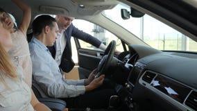 La familia feliz que se sienta en nuevo automóvil en salón, varón habla con el coche