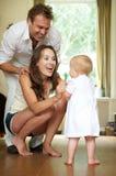 La familia feliz que sonríe como bebé toma las primeras medidas Imagen de archivo libre de regalías