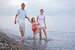 La familia feliz salpica el agua de los pies en la playa Imagenes de archivo