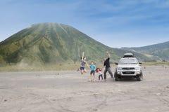 La familia feliz salta en desierto volcánico Fotografía de archivo