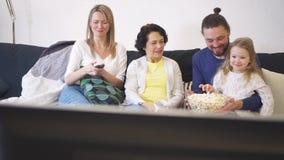 La familia feliz se está sentando en el sofá y la TV de observación con palomitas junta almacen de video