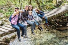 La familia feliz se est? sentando en un puente de madera en el medio de bosque fotos de archivo