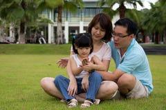 La familia feliz se sienta en campo de hierba Imagenes de archivo