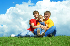 La familia feliz se sienta en hierba verde bajo el cielo Fotos de archivo