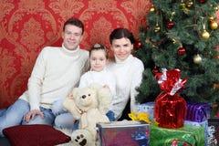 La familia feliz se sienta en piso con los regalos cerca del árbol de navidad Foto de archivo