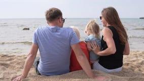 La familia feliz se sienta en la playa que mira el mar almacen de metraje de vídeo