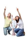 La familia feliz se sienta y destaca los dedos foto de archivo