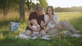 La familia feliz tiene primera comida campestre del verano en parque de la puesta del sol metrajes