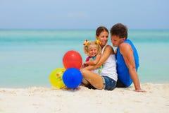 La familia feliz tiene un partido en la playa tropical fotografía de archivo
