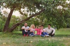 La familia feliz tiene un resto debajo de manzana del árbol Fotos de archivo libres de regalías