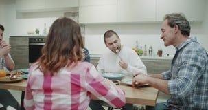 La familia feliz tiene una época junta en la tabla de cena ellos felices tomando un almuerzo junto y tener una conversación en almacen de video
