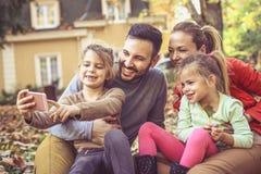 La familia feliz toma un autorretrato que se sienta en el patio trasero Foto de archivo