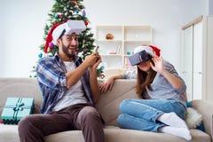 La familia feliz usando los vidrios del vr de la realidad virtual durante la Navidad Foto de archivo libre de regalías