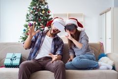 La familia feliz usando los vidrios del vr de la realidad virtual durante la Navidad Imágenes de archivo libres de regalías