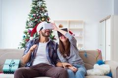 La familia feliz usando los vidrios del vr de la realidad virtual durante la Navidad Foto de archivo