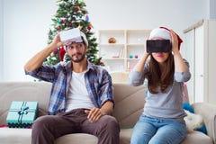 La familia feliz usando los vidrios del vr de la realidad virtual durante la Navidad Fotos de archivo