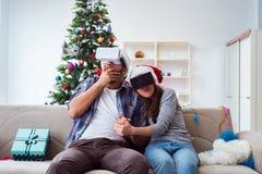 La familia feliz usando los vidrios del vr de la realidad virtual durante la Navidad Imagen de archivo