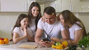 La familia feliz utiliza Smartphone foto de archivo libre de regalías