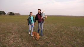 La familia feliz viaja con un perro en el campo con las mochilas Pap?, beb?, hija y perro casero, turistas trabajo com?n de a almacen de metraje de vídeo