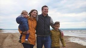 La familia feliz y amistosa está caminando con sus niños en la playa el día libre almacen de video