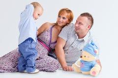 La familia feliz y peluche-lleva imagen de archivo