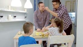 La familia gay con dos niños cocina la pizza junta en la cocina almacen de metraje de vídeo