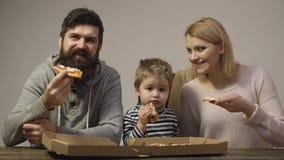 La familia goza de la pizza deliciosa Pizza sabrosa La mamá, el papá y el hijo están comiendo la pizza junta en el fondo blanco F almacen de metraje de vídeo