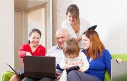 La familia goza en el sofá en sitio de la sala de estar con los ordenadores portátiles Fotos de archivo libres de regalías